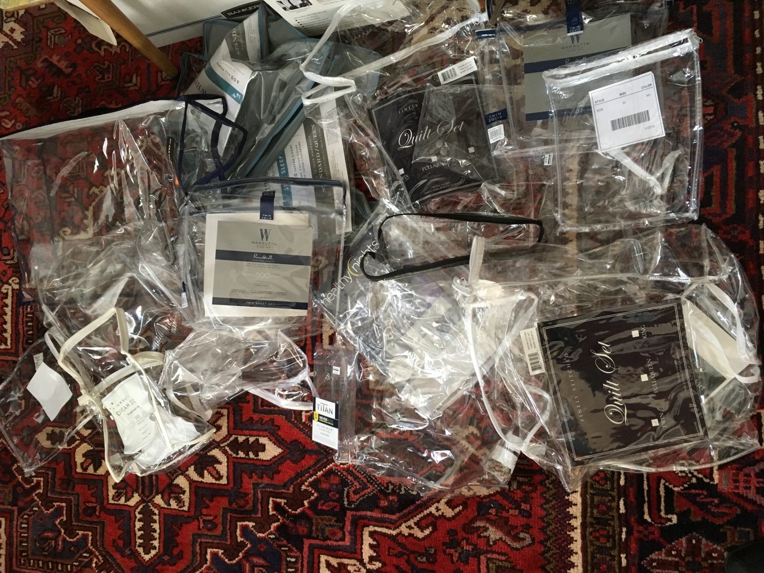 "A pile of empty plastic bags with labels like ""sheet sets"" on a red Persian rug"