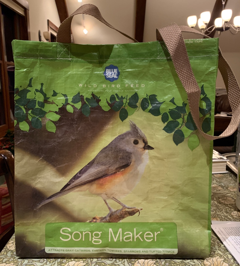 A green shopping bag with brown handles and a Tufted Titmouse image, with the words, Song Maker, sitting on a table.