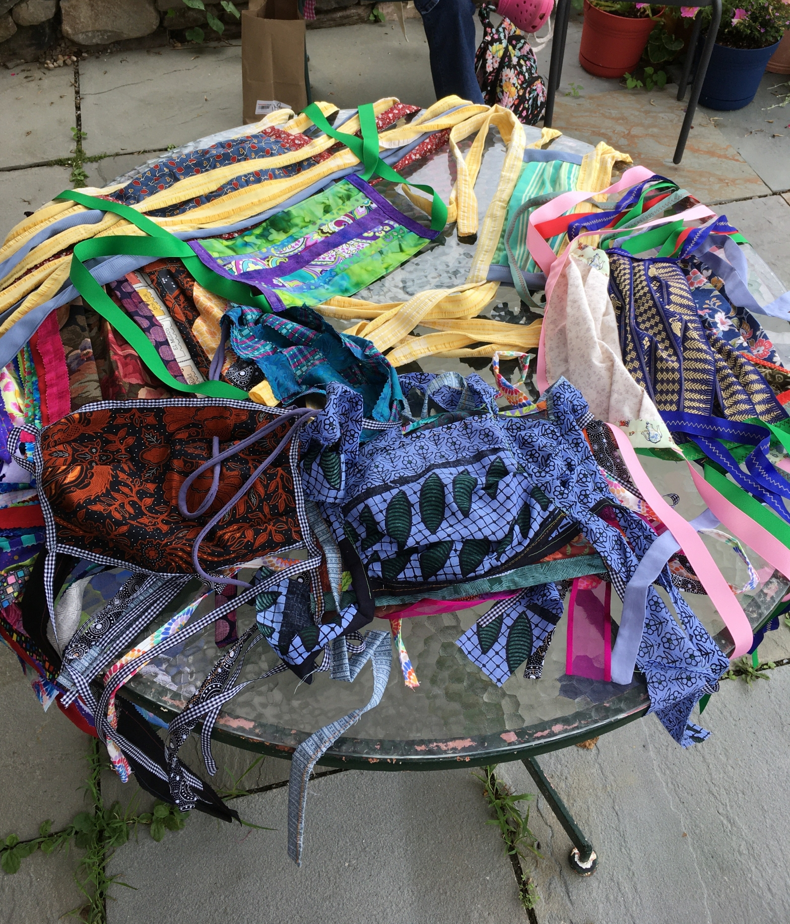 Pile of colorful sewn masks with ties on a round table.